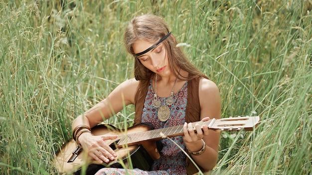 Schöne junge hippiefrau, die gitarre spielt, die auf gras sitzt