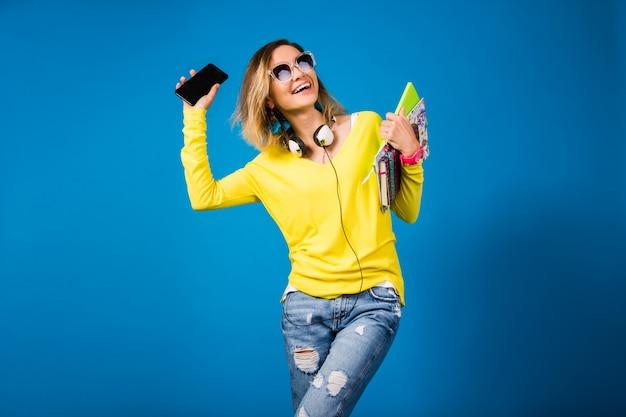 Schöne junge hipsterfrau, die bücher hält und smartphone betrachtet