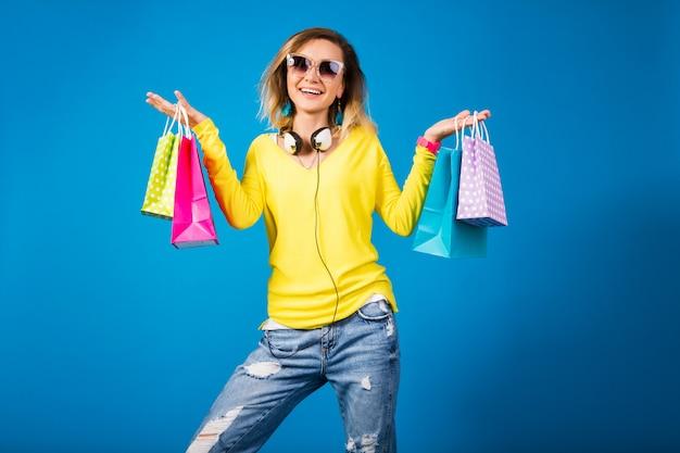 Schöne junge hipsterfrau, die bunte papiereinkaufstaschen hält
