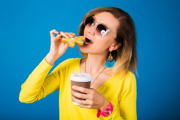 Schöne junge hipsterfrau, die kekse isst, kaffee trinkend