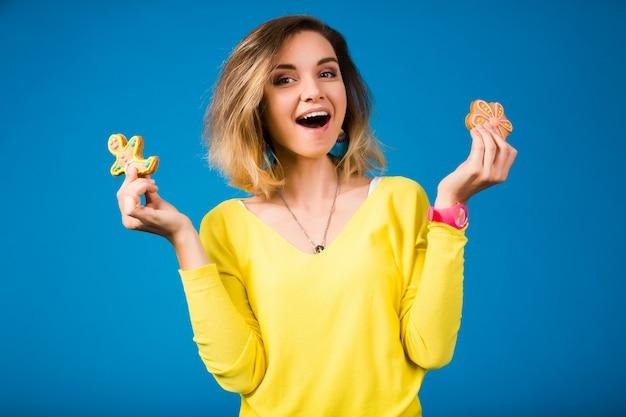 Schöne junge hipsterfrau, die kekse isst