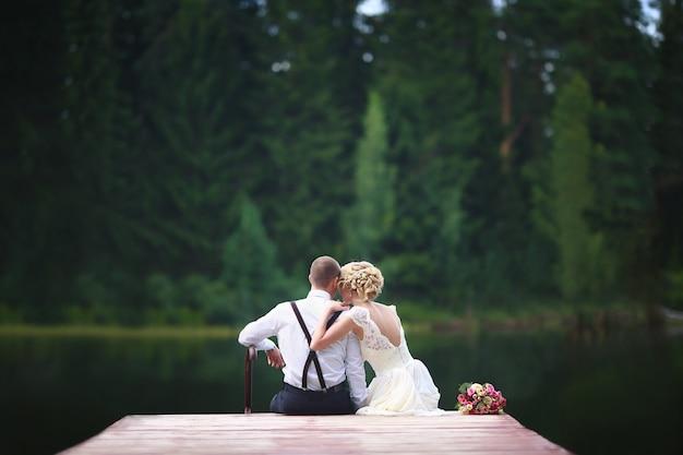 Schöne junge hochzeitspaare, die auf dem pier sitzen.