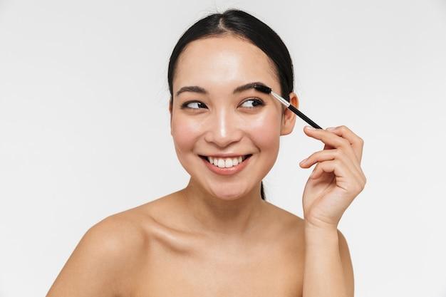 Schöne junge hübsche asiatische frau mit gesunder haut posiert nackt über der weißen wand, die brauenstyler hält.