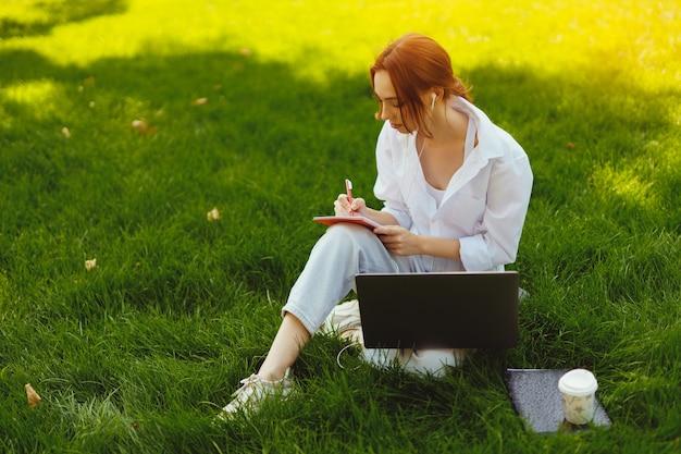Schöne junge hübsche rothaarige frau im park im freien mit laptop-computer für studium oder arbeit verkabelt ...