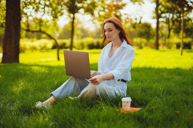 Schöne junge hübsche rothaarige frau im park im freien mit laptop-computer für studium oder arbeit