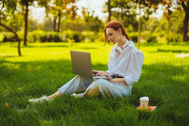Schöne junge hübsche rothaarige frau im park im freien mit laptop-computer zum studium oder online arbeiten...