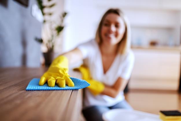 Schöne junge kaukasische blonde hausfrau mit gummihandschuhen auf händen, die auf dem boden im wohnzimmer sitzen und regal abstauben. wohnzimmer interieur. selektiver fokus zur hand.