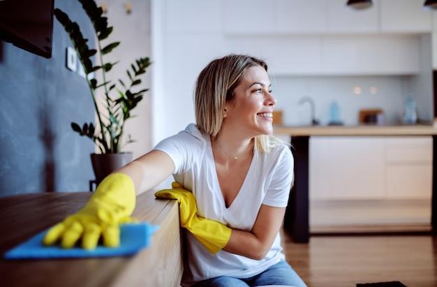 Schöne junge kaukasische blonde hausfrau mit gummihandschuhen auf händen, die auf dem boden im wohnzimmer sitzen und regal abstauben. wohnzimmer interieur.