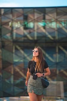 Schöne junge kaukasische brunettegeschäftsfrau außerhalb des bürogebäudehintergrundes des grünen glases. mit sonnenbrille und blick, vertikales foto
