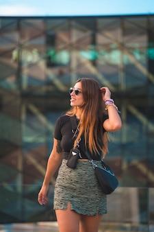 Schöne junge kaukasische brunettegeschäftsfrau außerhalb des bürogebäudehintergrundes des grünen glases. porträt des mädchens mit sonnenbrille