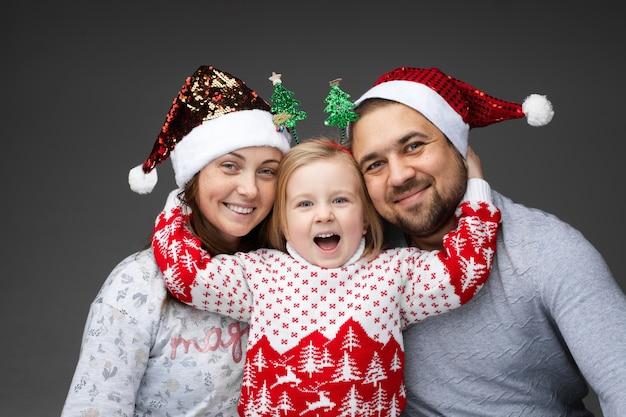 Schöne junge kaukasische familie von drei verbringt weihnachtszeit zusammen