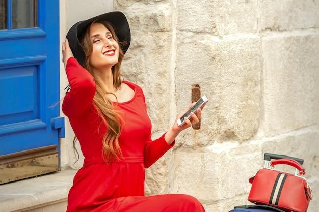 Schöne junge kaukasische frau, die auf der treppe durch die tür trägt schwarzen hut und langes rotes kleid mit reisekoffer und smartphone trägt