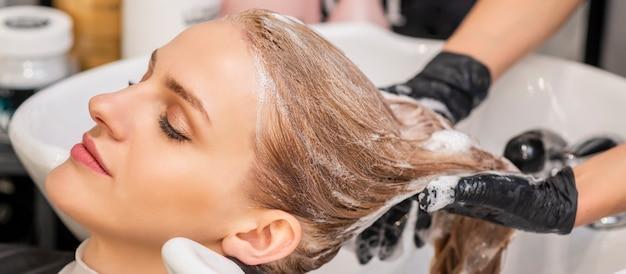 Schöne junge kaukasische frau, die empfängt, waschen ihre haare in einem friseursalon