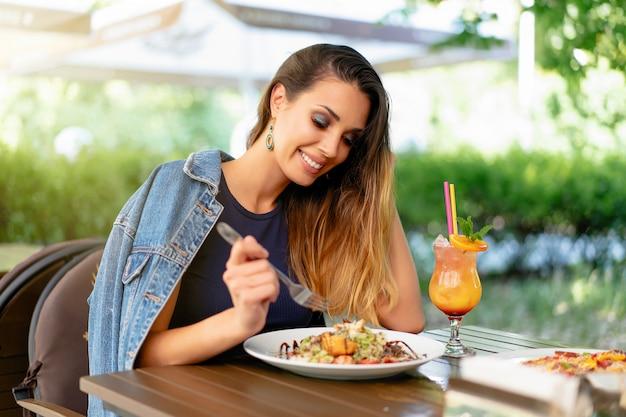 Schöne junge kaukasische frau, die frischen caesar-salat isst