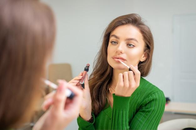 Schöne junge kaukasische frau, die glanz auf die lippen anwendet, die in den spiegel schauen