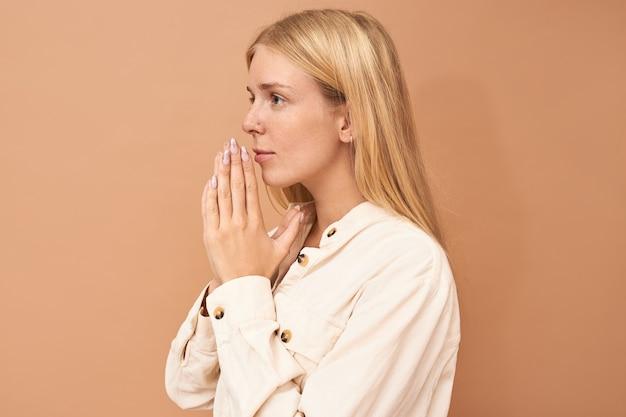 Schöne junge kaukasische frau, die hände auf ihr gesicht im gebet ihre augen voller hoffnung drückt. nettes entzückendes blondes mädchen, das für wellness betet