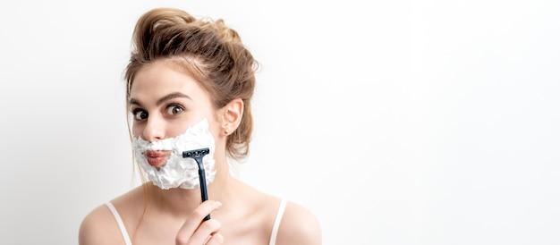 Schöne junge kaukasische frau, die ihr gesicht durch rasiermesser auf weißem hintergrund rasiert.