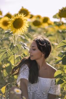 Schöne junge kaukasische frau, die in einem feld von sonnenblumen aufwirft