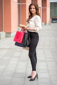Schöne junge kaukasische frau, die moderne stöckelschuhe zeigt, die nahe dem einkaufszentrum stehen