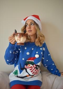 Schöne junge kaukasische frau im niedlichen blauen weihnachtsoutfit und in der weihnachtsmütze, die heiße schokolade trinkt