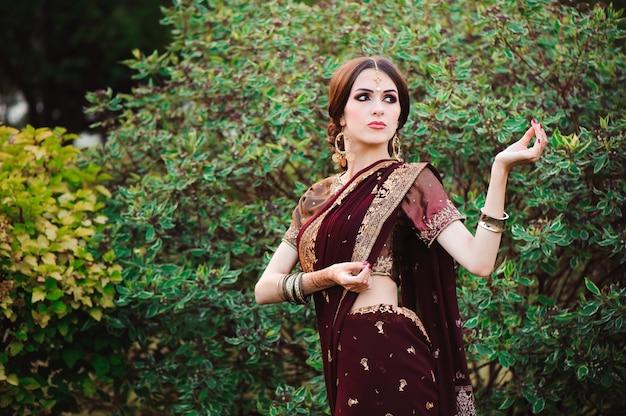 Schöne junge kaukasische frau im traditionellen indischen kleidungssari mit brautmake-up und schmuck und henna-tätowierung auf händen.