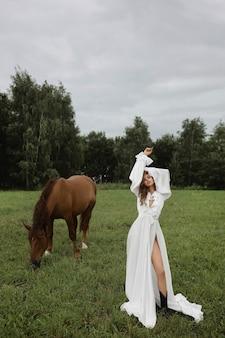 Schöne junge kaukasische frau im weißen kleid, das nahe dem braunen pferd auf der grünen wiese am sommertag aufwirft