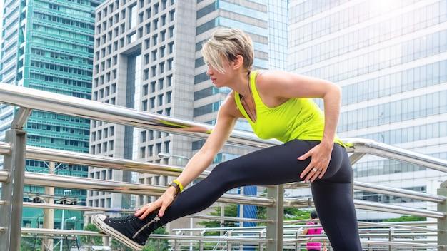 Schöne junge kaukasische frau in der fitnesskleidung, die übungen an der stadt im freien tut.