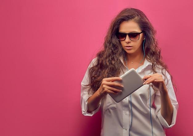 Schöne junge kaukasische frau in einem weißen hemd in den gläsern mit kopfhörern, eine weiße tablette in den händen auf einer rosa hellen wand haltend.