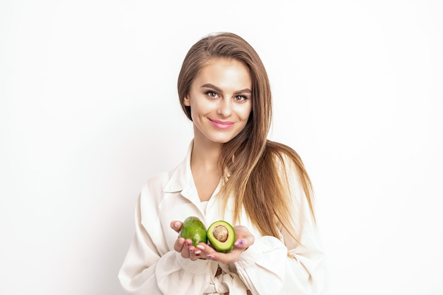Schöne junge kaukasische frau mit hälften der avocado auf weiß