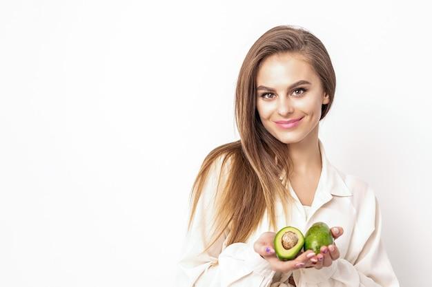 Schöne junge kaukasische frau mit hälften der avocado auf weißem hintergrund