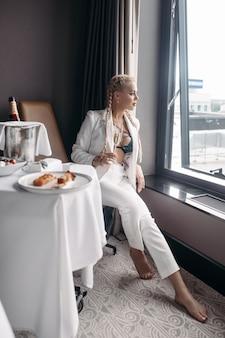 Schöne junge kaukasische frau mit langen blonden haaren, nettem gesicht, hellen ohrringen im weißen anzug