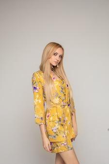 Schöne junge kaukasische frau mit langen blonden haaren und schönen make-up-posen für die kamera einzeln auf grauem hintergrund