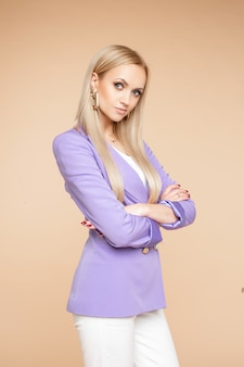 Schöne junge kaukasische frau mit langen blonden haaren und schönen make-up-posen für die kamera einzeln auf hellorangefarbenem hintergrund
