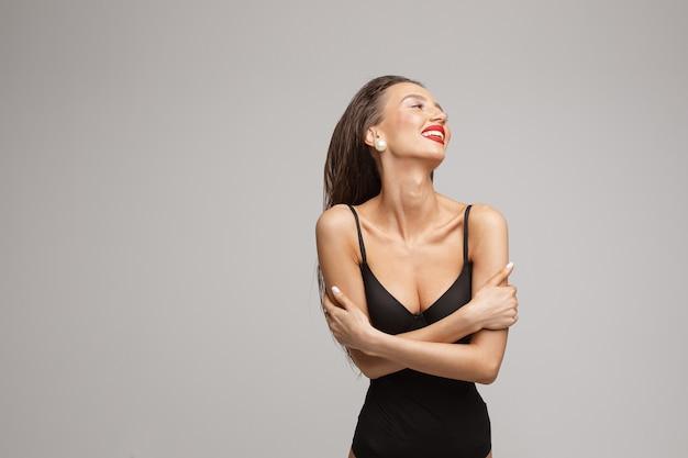 Schöne junge kaukasische frau mit langen dunklen haaren, schönem make-up, roten lippen im schwarzen badeanzug lächelt und sieht beiseite