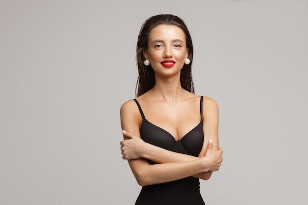 Schöne junge kaukasische frau mit langen dunklen haaren, schönem make-up, roten lippen im schwarzen badeanzug lächelt
