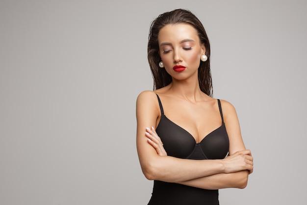 Schöne junge kaukasische frau mit langen dunklen haaren, schönem make-up, roten lippen im schwarzen badeanzug, mysteriöse blicke beiseite