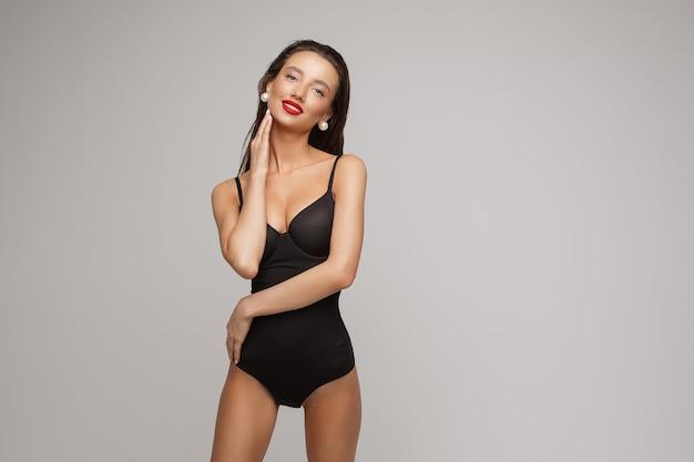 Schöne junge kaukasische frau mit langen dunklen haaren, schönem make-up, roten lippen im schwarzen badeanzug