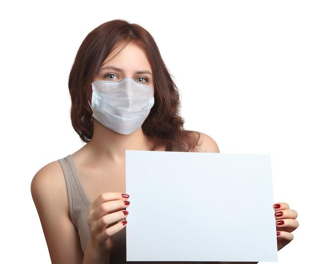 Schöne junge kaukasische frau trägt gesichtsmaske und hält ein leeres blatt papier in den händen während der covid 19-pandemie.