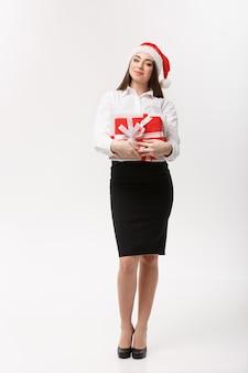 Schöne junge kaukasische geschäftsfrau des geschäftskonzepts mit weihnachtsmütze, die geschenkbox mit kopienraum auf seite hält