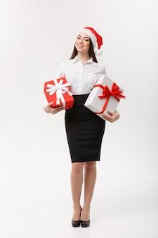 Schöne junge kaukasische geschäftsfrau des geschäftskonzepts mit weihnachtsmütze, die geschenkboxen mit kopienraum auf der seite hält