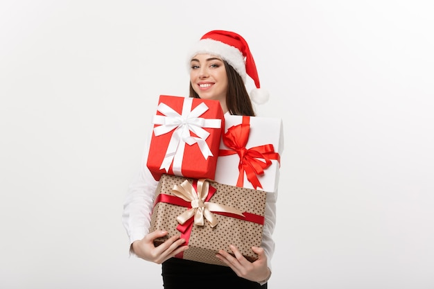 Schöne junge kaukasische geschäftsfrau des geschäftskonzepts mit weihnachtsmütze, die viele geschenkboxen mit kopienraum auf der seite hält