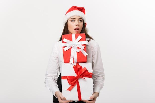 Schöne junge kaukasische geschäftsfrau des geschäftskonzepts mit weihnachtsmütze, die viele geschenkboxen mit überraschendem gesichtsausdruck hält