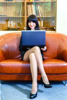 Schöne junge kaukasische geschäftsfrau, die an laptop arbeitet.