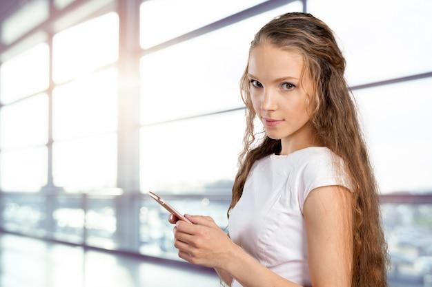Schöne junge kaukasische geschäftsfrau mit intelligentem telefon