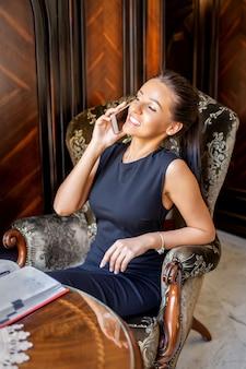 Schöne junge kaukasische lächelnde geschäftsfrau sitzt im sessel, der am telefon von ihrem wohnzimmer spricht