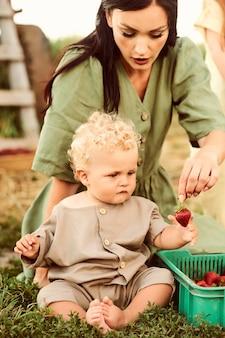 Schöne junge kaukasische mutter mit ihren kindern in einem leinenkleid mit einem korb erdbeeren sammelt eine neue ernte und hat spaß mit den kindern in der nähe des anhängers