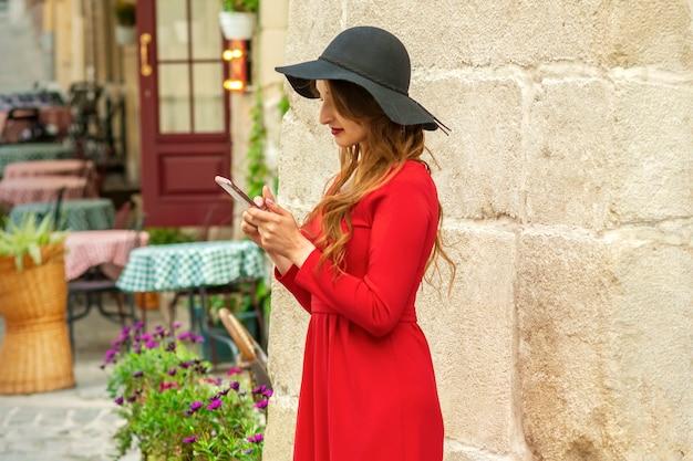 Schöne junge kaukasische reisefrau in einem roten langen kleid, das in einem smartphone auf der alten stadtstraße steht und schaut