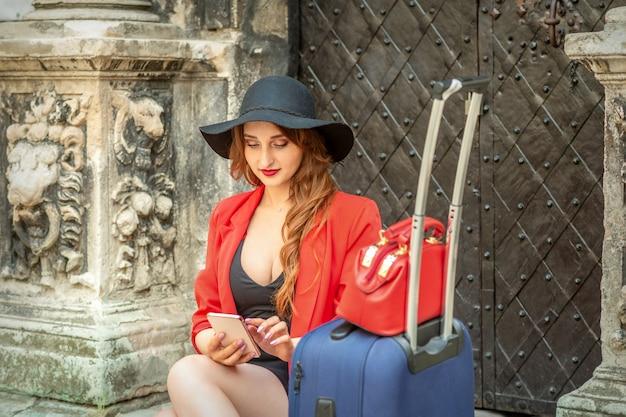 Schöne junge kaukasische reisefrau in einem schwarzen hut mit koffer, der in einem smartphone auf der alten stadtstraße sitzt und schaut