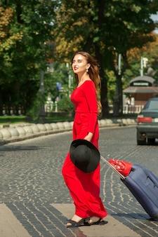 Schöne junge kaukasische touristenfrau mit einem koffer im roten langen kleid kreuzt die straße durch einen zebrastreifen auf der stadtstraße im freien