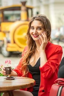 Schöne junge kaukasische touristenfrau spricht am telefon, das am tisch im straßencafé in einer europäischen stadt sitzt